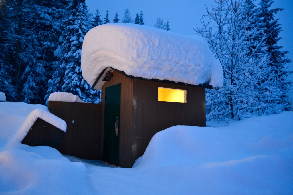 Massive amounts of snow, as shown by the giant snow hat on top of this roadside outhouse